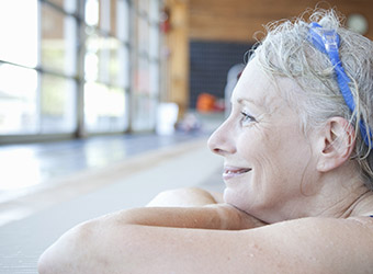 Mature woman resting on edge of pool, smiling