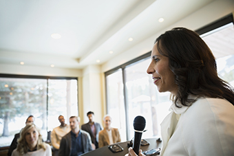 Businesswoman with microphone leading conference